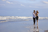 Romantic Man and Woman Couple Walking On A Beach