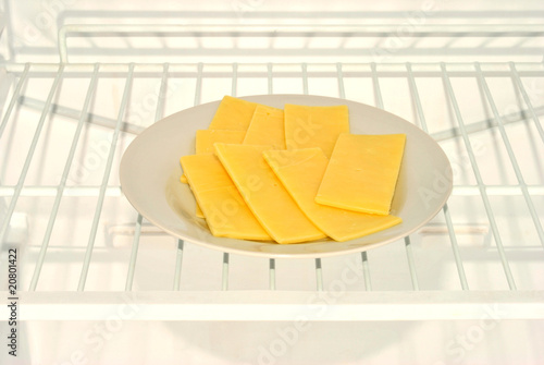 some slices cheese on a plate in a fridge