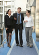 group of three persons talking on the corridor in office space