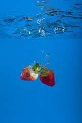 two strawberries splashing