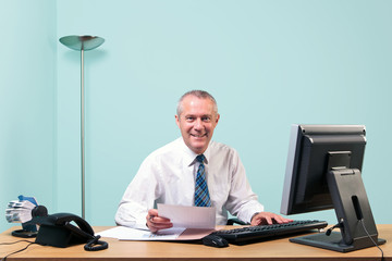 Mature businessman sat at his office desk
