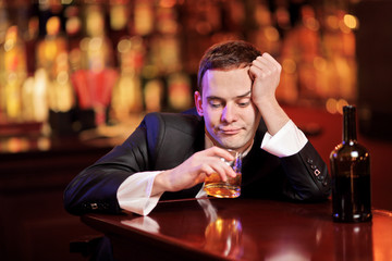 Young drunk man drinking whiskey in the bar
