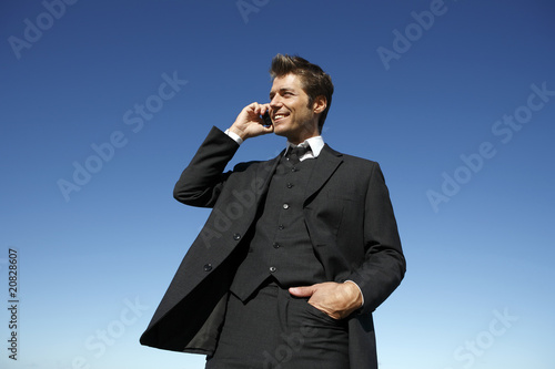Young businessman in suit on the phone outdoors