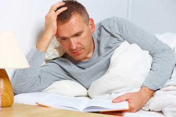 Sleepless man reading a book