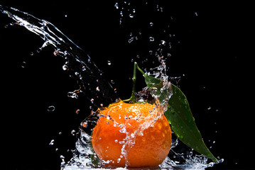 Tangerine with green leaves and water splash isolated on black