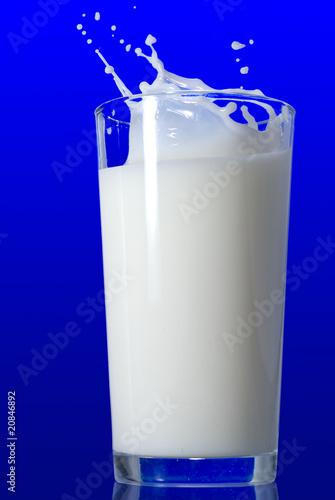 Leinwandbild Motiv Milk splash isolated on blue