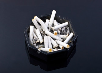 black ashtray with cigaretes on black table
