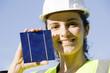 Eine hübsche Frau hält eine Solarzelle Richtung Sonne