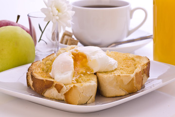 Fresh Poached Egg on Toast with Coffee and orange juice
