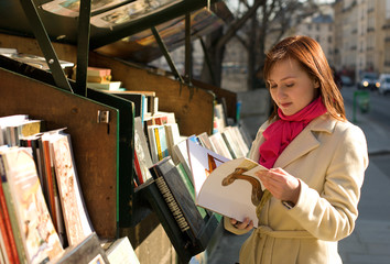 Beautiful woman in Paris selecting a book in an outdoor booksel