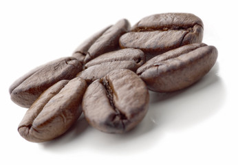 Seven coffee beans on the white background. Soft focus.