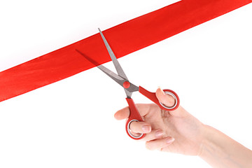 Red ribbon, scissors and hand isolated on white.