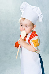 Little child in the cook costume in the white hat and with spoon