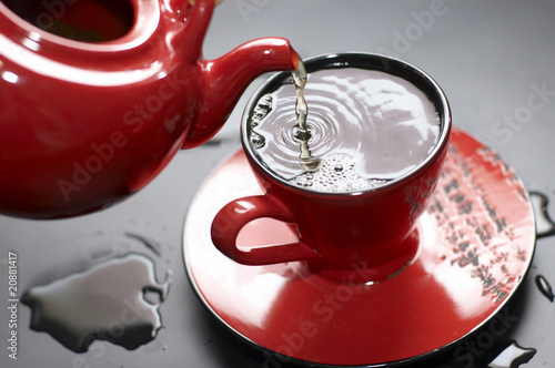 Plakat Flowing tea into red cup