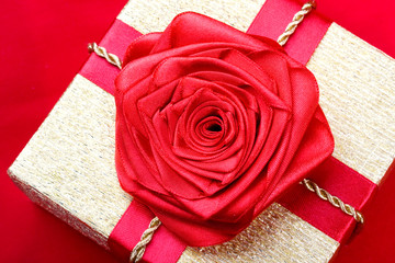 Gold box on a red background with a red ribbon rose