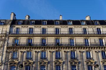 Vieil immeuble parisien en pierre, ciel bleu.