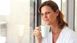 Cute mature woman drinking a cup of coffee