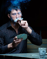 Young handsome gambler smoking