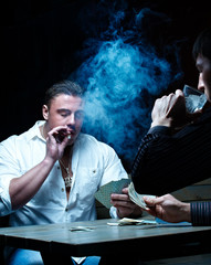 Two gamblers smoking and drinking