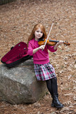 Beautiful little girl with long red hair outdoors with violin