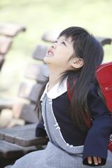 ベンチに座り上を見上げる小学生女子