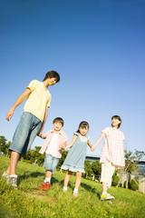 手を繋いで公園を散歩する家族