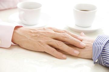 重なり合う手とコーヒーカップ