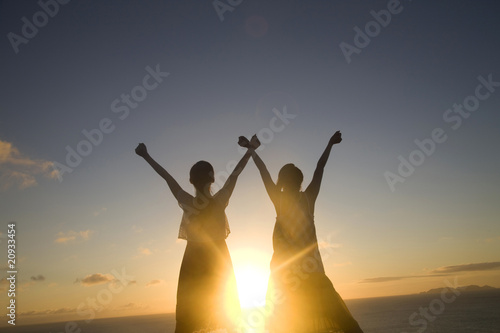 夕暮れに両手を空に広げる女性2人のシルエット