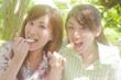 新緑に囲まれたカフェでスイーツを食べる女性2人