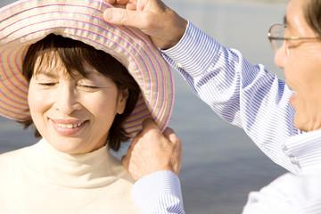 妻の帽子を直している夫