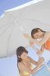 ビーチパラソルを砂浜に建てようとしている水着女性2人
