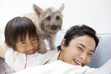 父親の背中に乗る子供と犬