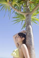 椰子の木に寄りかかりながら空を見上げる水着女性