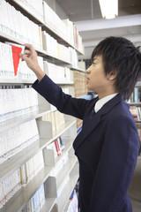 本を手に取る男子高校生