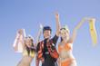 青空の下でフィンを持って記念撮影をする水着女性2人とウェットスーツを着た男性