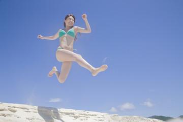 砂浜でジャンプする水着女性