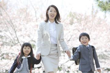 桜の下を歩く小学生男女と母親