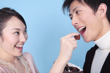 チョコレートを男性に食べさせる女性