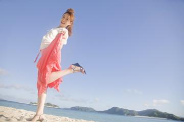 海辺ではしゃぎながら微笑む女性