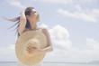 麦わら帽子を持ってビーチに立つ女性