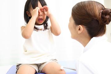 怪我をした女の子に消毒をする看護師