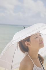 ビーチで日傘を差して目を閉じる女性