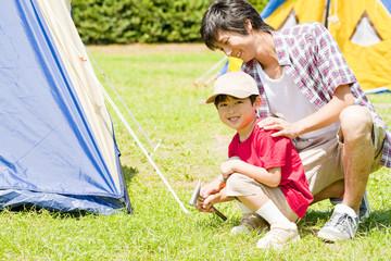 父親と一緒にテントをたてる男の子