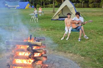 キャンプ中の家族とキャンプファイヤー