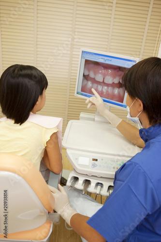 モニターで女の子に治療の説明をする男性歯科医