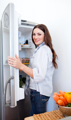 Smiling woman looking for something in the fridge
