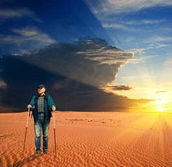 traveler in a desert by a sunset