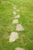 Stones path trough the grass, with an intersection at the end poster