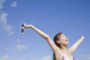 サングラスを持って万歳をしている水着姿の女性