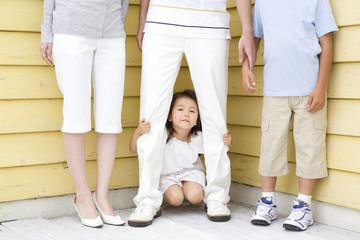 父親の足元に隠れる女の子